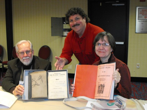 Jeanette Thompson and Lenny Bertrand (standing) of Tulane University exhibit some repaired scores from Tulane's music library with John Druesedow.